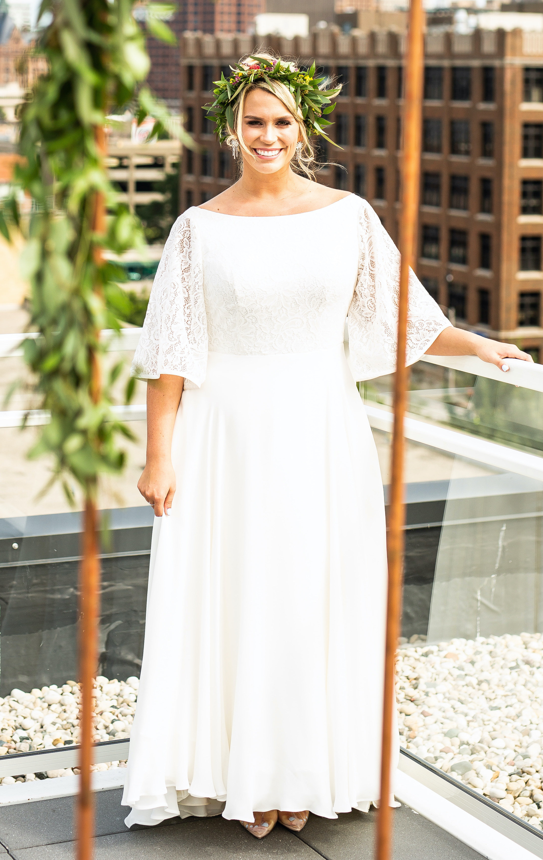 Anomalie specialized in making online wedding dresses for plus sized brides, including dresses with boat neckline and bell sleeves.