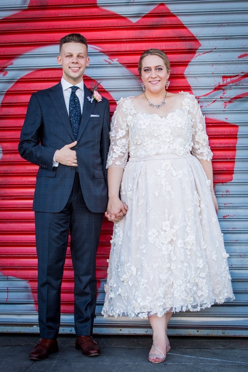 Anomalie specialized in making online wedding dresses for plus sized brides, including dresses with tea length skirt and 3d floral lace.