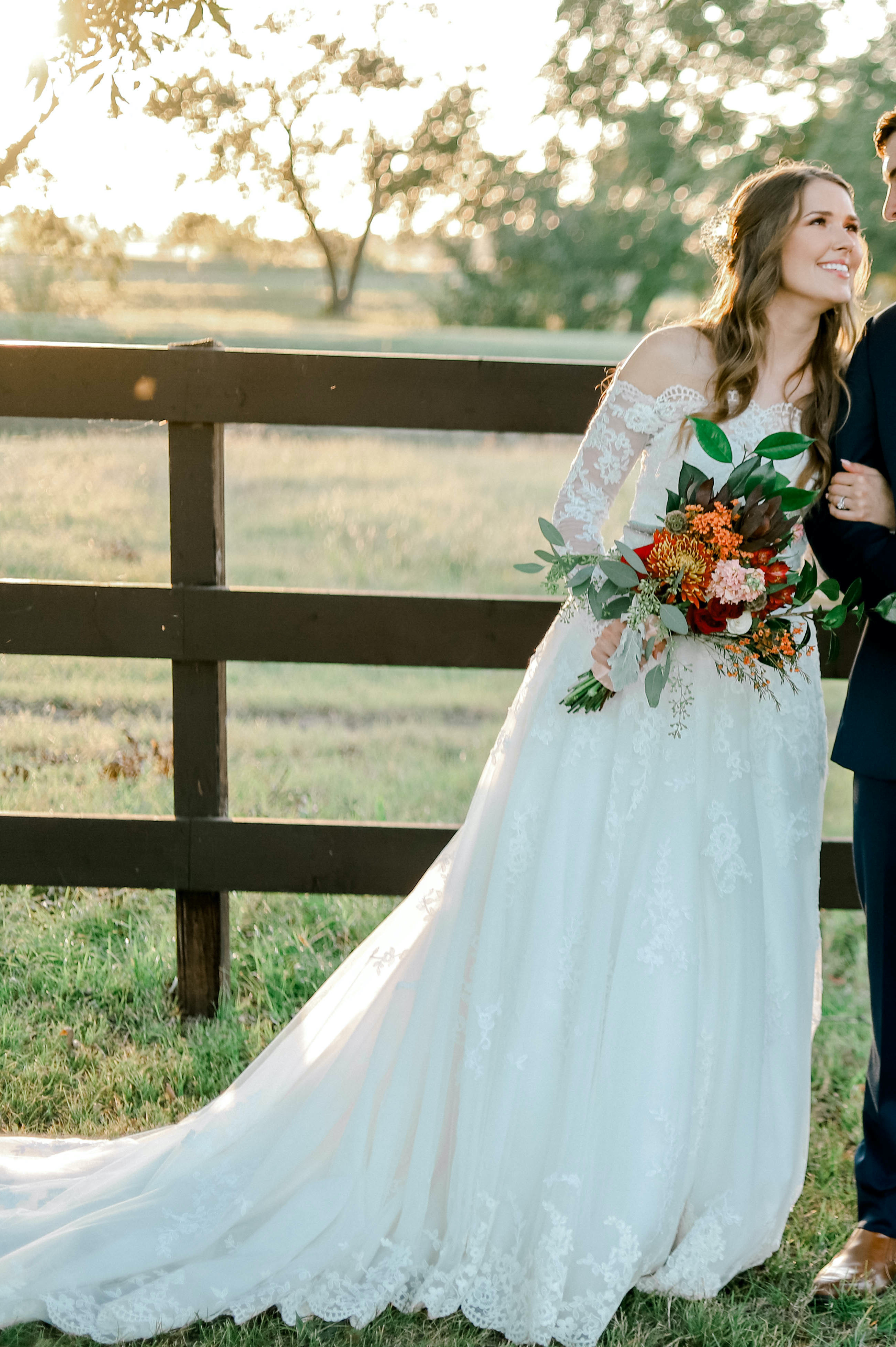 Anomalie creates online custom wedding dresses, including boho gowns with long lace off-the-shoulder sleeves and flowy skirt.