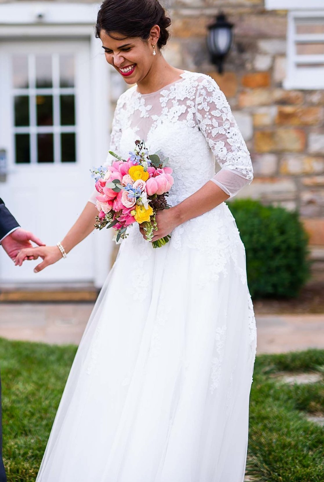 Anomalie creates online custom wedding dresses, including boho gowns with long lace sleeves and flowy skirt.